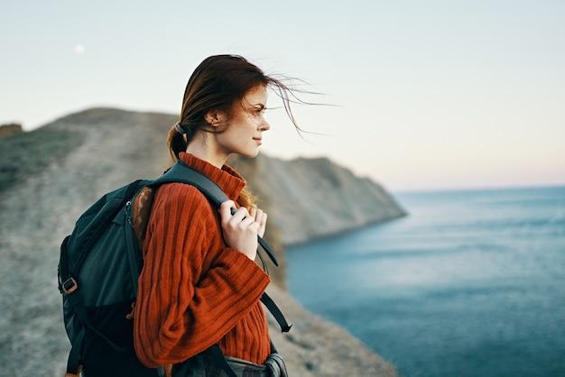 Frau touristin mit einem rucksack in einem pullover ruhen in den bergen in der nähe des meeres und betrachten