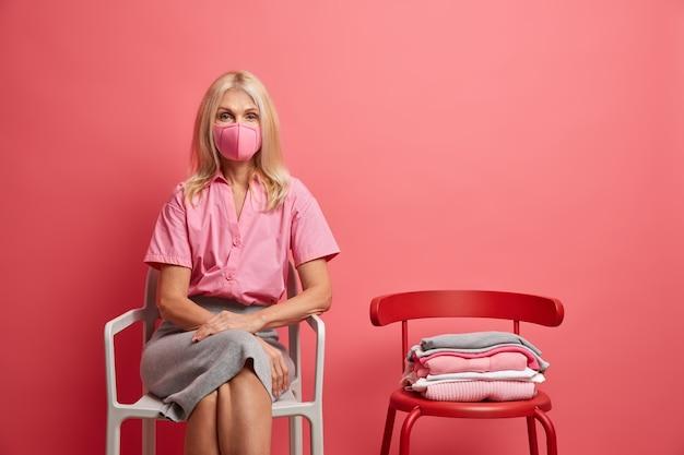 Frau trägt anti-virus-schutzmaske bleibt während der quarantäne zu hause und versucht, die epidemie zu stoppen, sitzt auf einem stuhl isoliert auf rosa