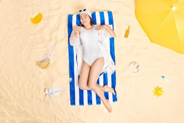 Frau trägt badehut und badeanzug sonnenbrille auf der stirn macht koreanische wie schildposen am sandstrand während der sommerferien genießt schönes wetter und urlaub