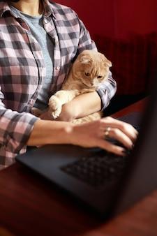 Frau trägt bequemen stil arbeitet an einem schwarzen notizbuch, laptop und katze liegt auf ihrem schoß