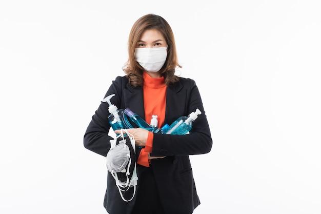 Frau trägt eine maske zum schutz vor coronavirus und hält handwaschgel.