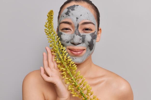 Frau trägt eine nährende gesichtsmaske aus ton auf, die eine pflanze für die kosmetikproduktion hält, kümmert sich um hautposen mit nackten schultern im innenbereich auf grauem studio