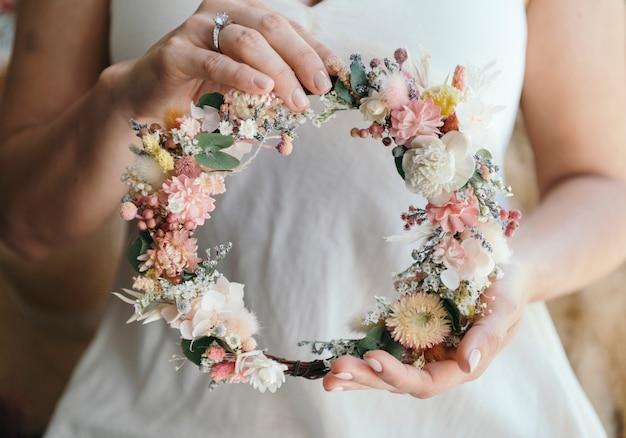 Frau trägt einen verlobungsring mit einem blumenkranz aus exotischen blumen