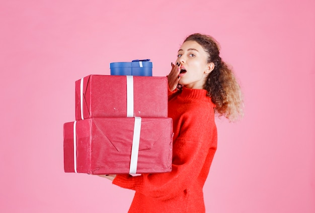 Frau trägt einen vorrat an großen geschenkboxen und sieht überrascht aus.