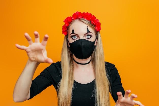 Frau trägt halloween-kostüm mit schwarzer maske