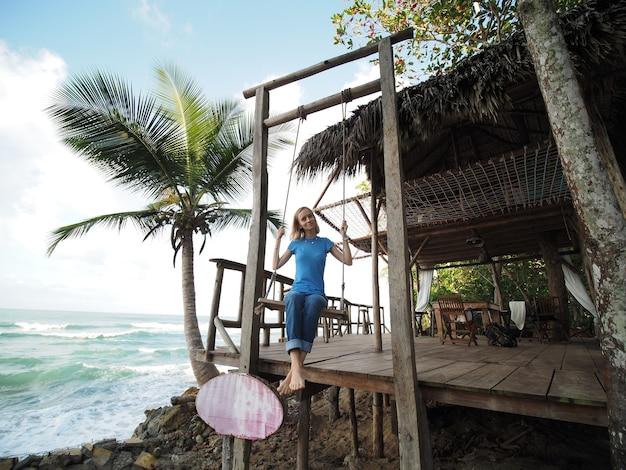 Frau trägt jeans und hat spaß auf schaukel im ozeanufer. dominikanische republik.