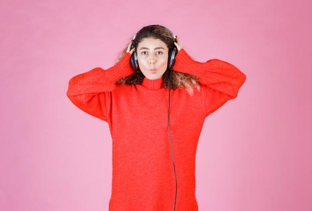 Frau trägt kopfhörer, um die musik zu hören.