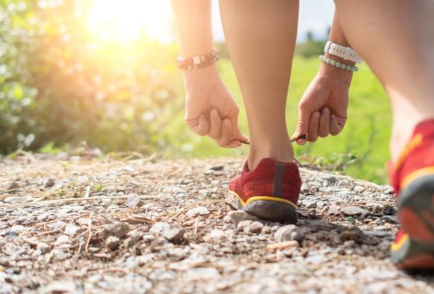 Frau trägt laufschuh zum gehen und laufen auf grünem hintergrund der natur. gesundheitsübungskonzept.
