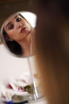 Frau trägt make-up im badezimmer auf