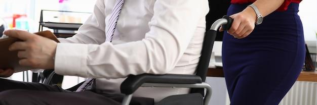 Frau trägt mann im anzug auf rollstuhlarbeitsplatz