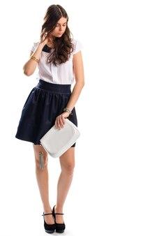 Frau trägt marinerock. weiße clutch und bluse. modisches frühlingsoutfit. designerschuhe und klassische uhr.