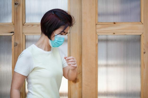 Frau trägt maske, die die tür mit dem ellbogen für schutzinfektion covid-19 öffnet