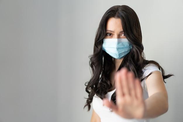 Frau trägt maske zum schutz vor krankheit und zeigt stop-hand-geste für stop-corona-virus