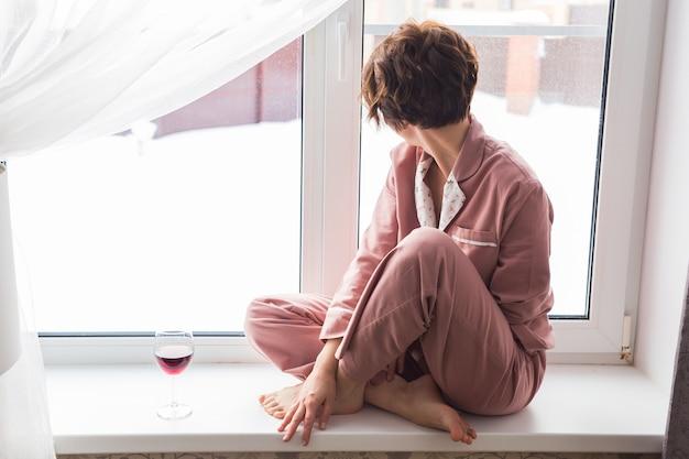 Frau trägt pyjama mit einem glas rotwein sitzt auf der fensterbank in der nähe des schönen fensters zu hause.