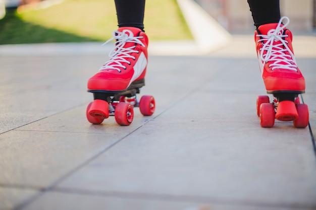 Frau trägt rollerskates reiten auf bürgersteig