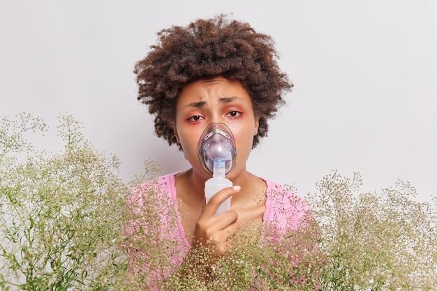 Frau trägt sauerstoffmaske, inhalation hat rote augen, leidet an einer pollenallergie, die über weiß isoliert ist