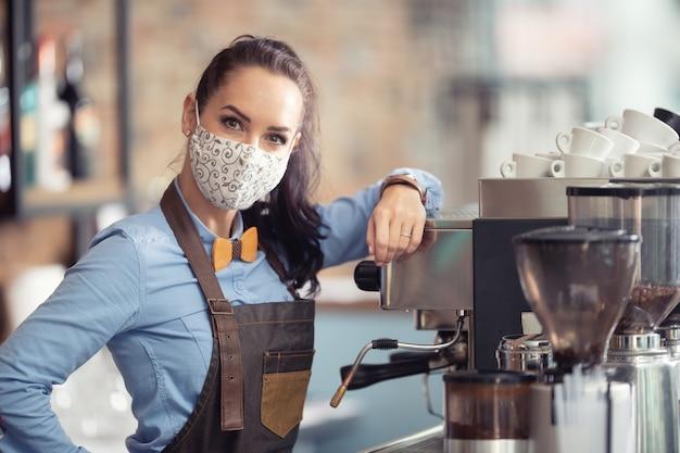 Frau trägt schutzmaske bei der arbeit und arbeitet als kellnerin in einem kaffeehaus.