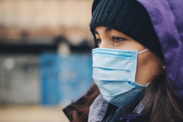 Frau trägt schutzmaske im freien. maske gegen infektionskrankheiten und grippe. gesundheitskonzept. stoppen sie die infektion. coronavirus quarantäne.