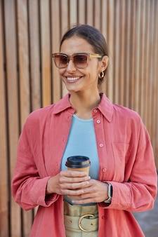 Frau trägt sonnenbrille freizeitkleidung hält einweg-tasse kaffee genießt freizeit-posen auf holz