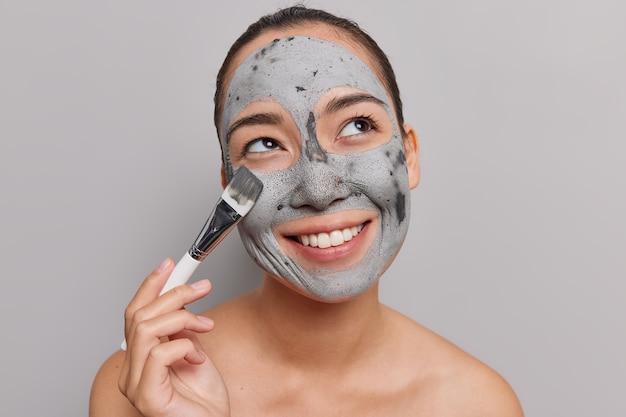 Frau trägt tonmaske mit pinsel auf lächelt breit hat weiße perfekte zähne genießt hautpflegeverfahren steht ohne hemd drinnen auf grauer studiowand. wellness-verwöhnung
