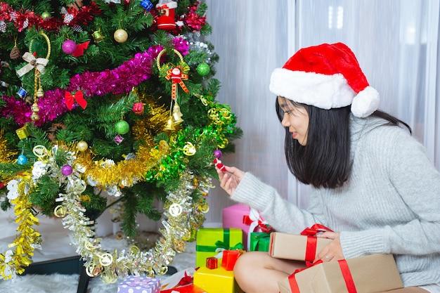 Frau trägt weihnachtsmütze glücklich mit weihnachtsgeschenk