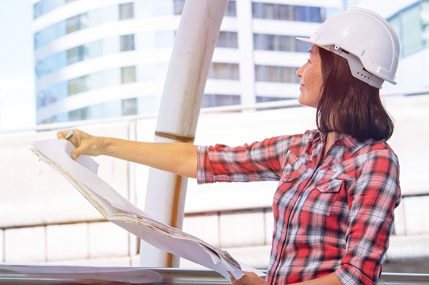 Frau trägt weißen sicherheitshut arbeitet an der baustelle