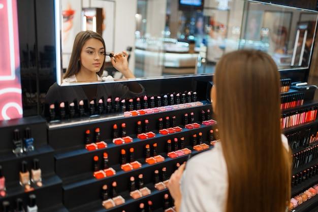 Frau trägt wimperntusche am spiegel im kosmetikgeschäft auf. käufer an der vitrine im luxus-beauty-shop-salon, kundin im modemarkt