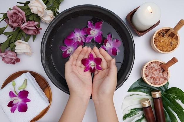 Frau tränkt ihre hände in schüssel mit wasser und blumen, spa-behandlung und produkt für weibliche füße und hand-spa, massagekiesel, parfümiertes blumenwasser und kerzen, entspannung. flach liegen. draufsicht.