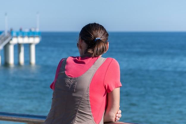 Frau träumt vom reisen und schaut aufs meer. hintere hintere ansicht, kopienraum. warten auf einen liebhaber oder ehemann. sonniges wetter und sauberes blaues meer.