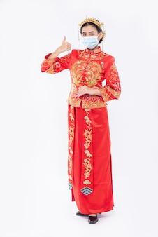 Frau tragen cheongsam anzug und maske zeigen den besten weg zum einkaufen zum schutz von krankheiten
