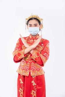 Frau tragen cheongsam anzug und maske zeigen menschen, die keine maske tragen, können nicht kommen, um im chinesischen neujahr einzukaufen