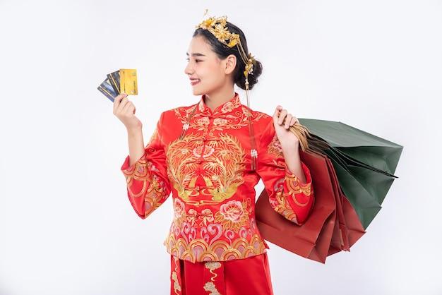Frau tragen cheongsam anzug verwenden kreditkarte, um viele geschäfte im chinesischen neujahr einzukaufen