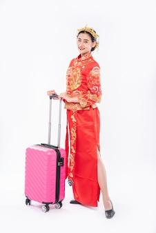 Frau tragen cheongsam anzug verwenden rosa reisetasche für die reise im chinesischen neujahr