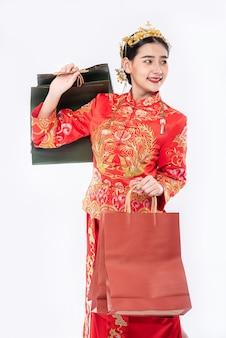 Frau tragen cheongsam anzuglächeln mit papiertüte vom einkaufen im chinesischen neuen jahr