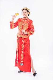Frau tragen cheongsam bekommen die kreditkarte vom vater, um im chinesischen neujahr zu verwenden