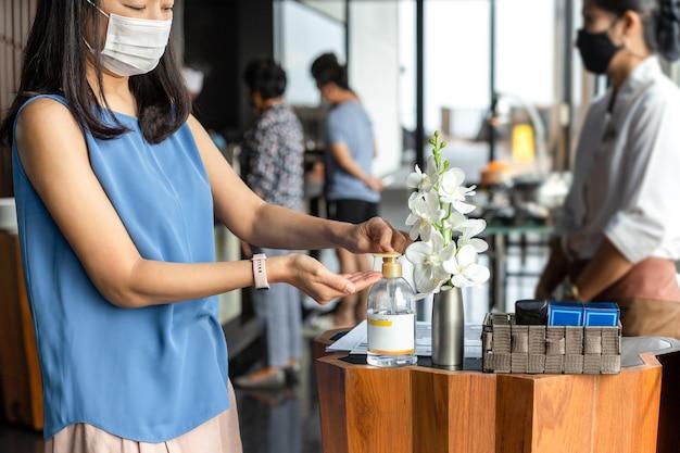 Frau tragen gesichtsmaske, die alkoholgel drückt, das ihre hand für covid19 reinigt