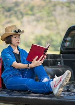 Frau tragen hut und liest das buch auf pickup