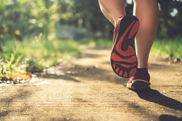 Frau tragen laufschuh auf gehen und laufen auf naturgrünem hintergrund. gesundheitsübungskonzept.