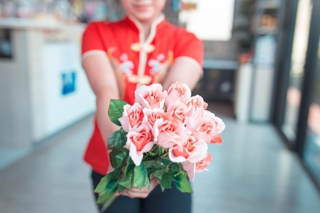 Frau tragen rotes hemd, das rosa rosenstrauß hält, für spezielles zeitkonzept.