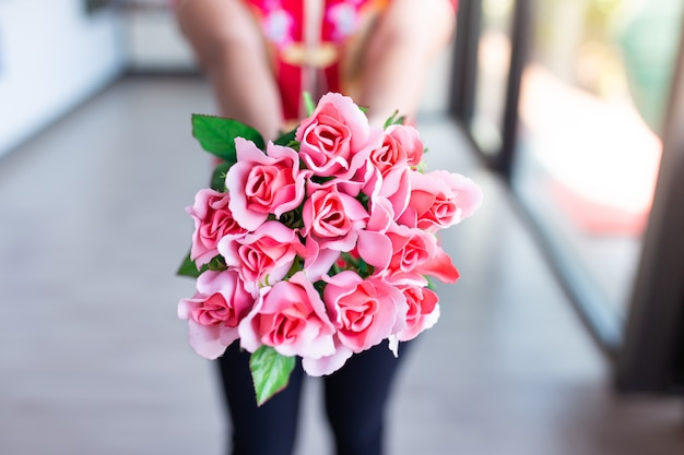 Frau tragen rotes hemd, das rosa rosenstrauß hält. valentinstag konzept