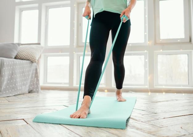Frau trainiert auf matte mit gummiband