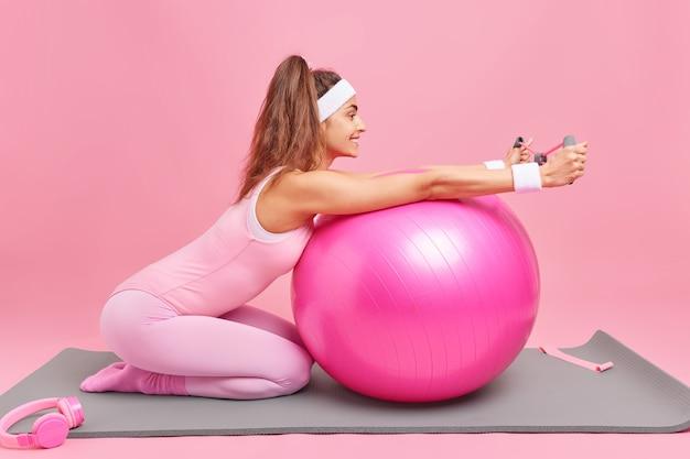 Frau trainiert hände mit expander-posen auf knien bei fitnessmattenzügen mit schweizer ball in activewear