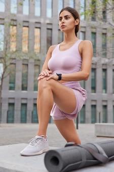 Frau trainiert im freien in sportkostüm gekleidet trägt turnschuhe posen in der stadt verwendet karemat für fitnesstraining