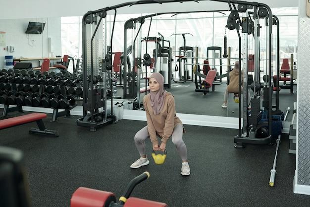 Frau trainiert mit kettlebell