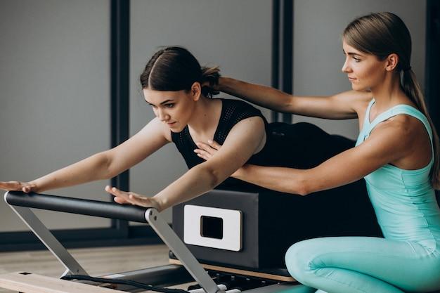 Frau trainiert pilates auf dem reformer