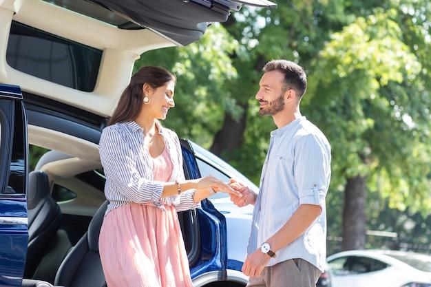 Frau treffen. der bärtige, liebevolle ehemann trifft seine ansprechende, strahlende frau in der nähe des autos