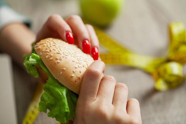 Frau trifft eine wahl zwischen schädlichen und gesunden lebensmitteln