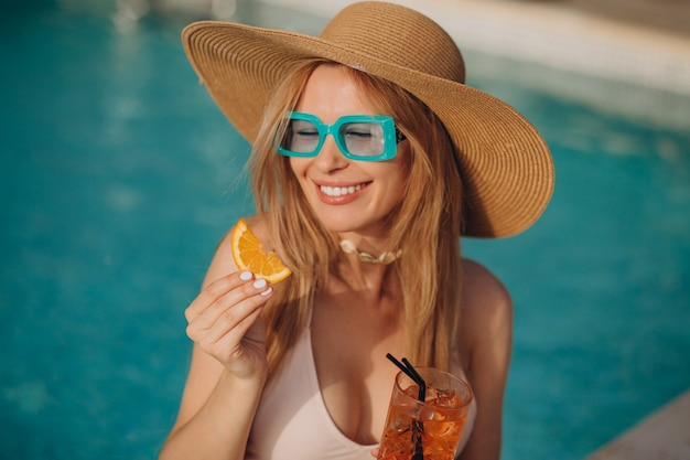 Frau trinkt alkoholcocktail am pool