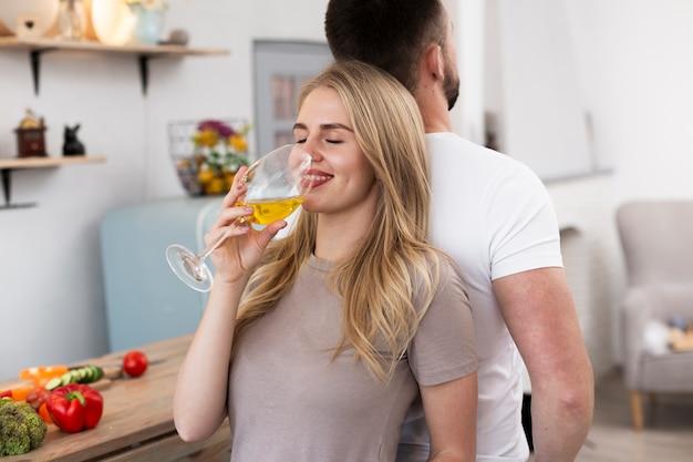 Frau trinkt aus einem glas zurück, um ihren mann zu unterstützen