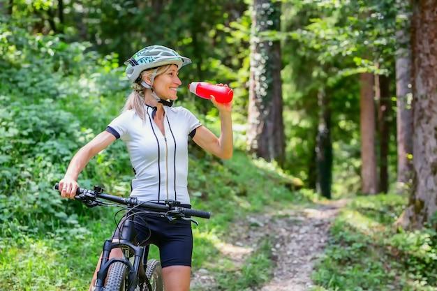 Frau trinkt aus ihrer wasserflasche auf mountainbike
